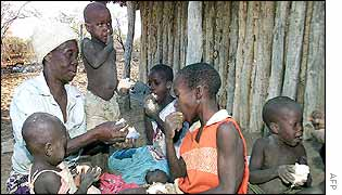 A grandmother feeds donated bread to her family in Zimbabwe