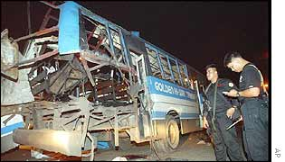 Police guard the remains of the bus