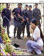 Women pray at the ruins as armed police look on