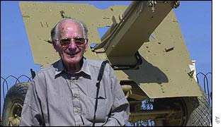 Michael Coustant, a British captain during WWII smiles in front of a British 17 PDR Antitank gun