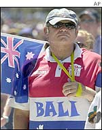 Man wearing a Bali shirt and carrying the Australian flag