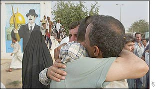Iraqi prisoner and his relative hug each other