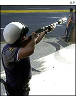 Riot policeman aims tear-gas round in Caracas