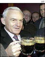 Polish Prime Minister Leszek Miller toasts the result in Warsaw with Guinness