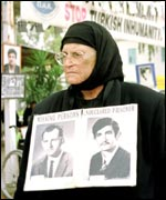 Greek-Cypriot woman with pictures of her missing relatives
