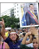 Chavez supporter holding a placard of the Venezuelan president at a rally in his support