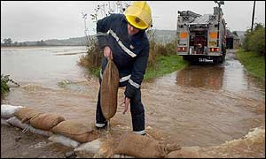 Firefighter laying sandbags