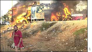 A man stands near the burning bus