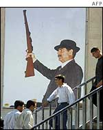 Iraqis in front of a poster of President Saddam
