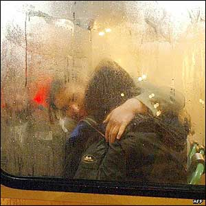 A released hostage (black jacket) is comforted by police inside a police bus
