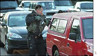 An armed officer checks a vehicle near Washington