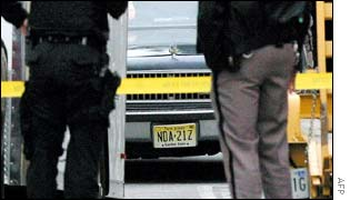 Law enforcement officers, watch as a car bearing New Jersey license plate number NDA-21Z is pushed into a garage