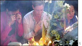 Balinese and a foreigner pray in front of flowers and candles during a memorial service in Denpasar