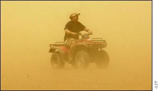 An Australian farmer rides through a duststorm