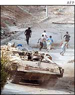 Children run away from an armoured vehicle in Jenin