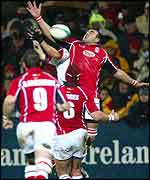 Llanelli's Chris Wyatt just beats Ulster Gary Longwell to the ball