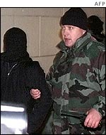 Unidentified Chechen rebel (left) being led away by Russian special forces agent