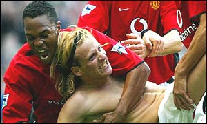 Manchester striker Diego Forlan is mobbed by his team-mates after equalising