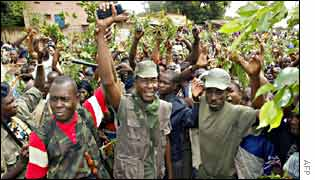 The rebel leader in Ivory Coast's north-west, Dosso (C), and his men are cheered by the crowd