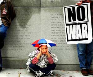 Girl sits by Vietnam War Memorial in Charlotte, North Carolina as a man holds a placard saying