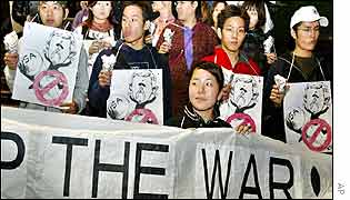 Anti-war protesters in Japan hold cartoons of Bush and a