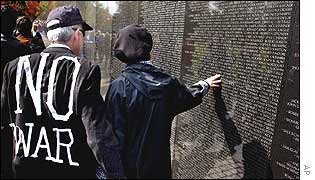 Two anti-war protesters pause to read the names on the Vietnam War Memorial in Washington DC