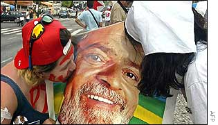 Two Lula supporters kiss a poster depicting him