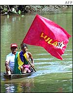 Two men wave Lula flag while in a boat in the northern Brazilian state of Para