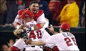 Anaheim Angels catcher Bengie Molina (L) jumps into the arms of closing pitcher Troy Perceval (centre) as Troy Glaus rushes to celebrate