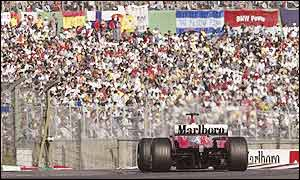 Michael Schumacher passes in front of the packed grandstands in Japan