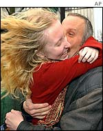 A father embraces his daughter, a former hostage, on her release from hospital on Monday