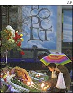 A woman leaves flowers at a memorial for the victims of the theatre siege