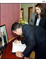 King Abdullah and Queen Rania signing condolence book