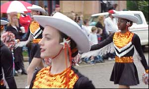 Cheerleaders, one white and one black, march in a Texas parade