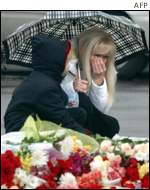 A woman weeps after laying flowers in front of the theatre