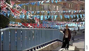 A woman walks in a street decorated with pre-election flags in the village of Kecioren near Ankara