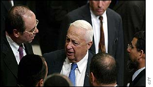 Ariel Sharon (centre) talks to coalition members after budget vote