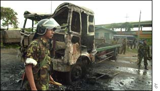 A Sri Lankan soldier walks past a burnt lorry after the rioting