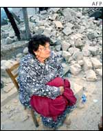 An old woman sits near the remains of her house