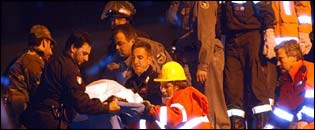 Rescuers remove the body of a child from the wreckage of the school
