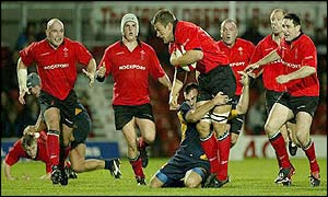 Gareth Llewellyn is smothered by a Romanian tackle as the Welsh forwards attack