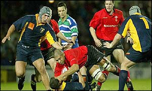 Welsh captain Colin Charvis is blocked by Romania scrum-half Petre Mitu