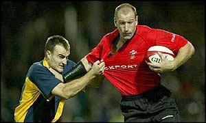 Welsh winger Gareth Thomas attempts to hand off a tackle from Romania's Gabriel Brezoianu