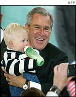 Bush poses for a photograph with baby while campaigning in New Hampshire