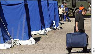 Earthquake victim carries his belongings by a row of tents near San Giuliano Di Puglia
