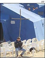 Earth quake victim sits under a wooden cross in a tent camp