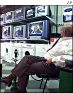 A shopkeeper watches an Al-Jazeera broadcast