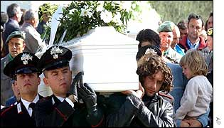 Italian police carry the coffin of one of the victims