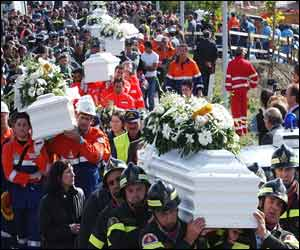 Italian rescuers and armed service workers carry the coffins of victims in procession