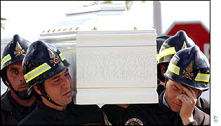 Firefighters weep as they carry a coffin during the funeral procession